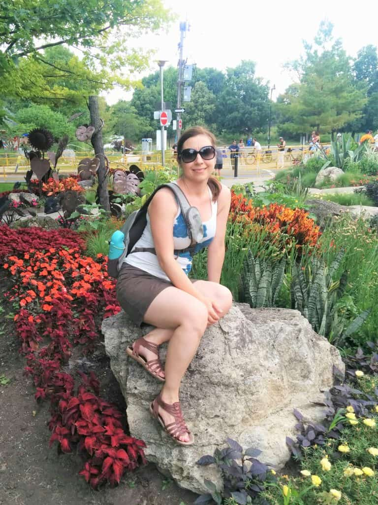 girl sitting on a rock surrounded by flowers in high park