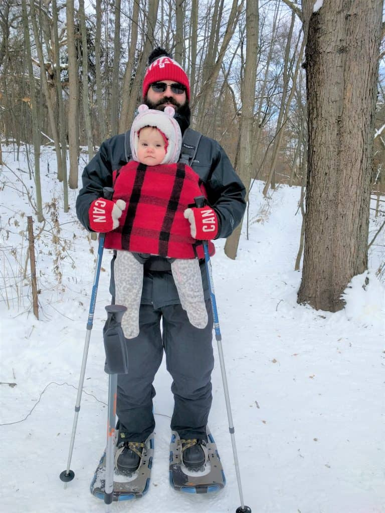 man hold baby while snow shoeing in high park