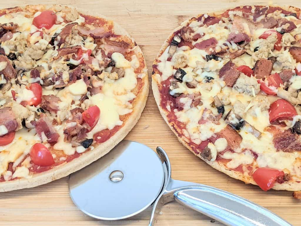 2 pizzas on a cutting board with a pizza slicer