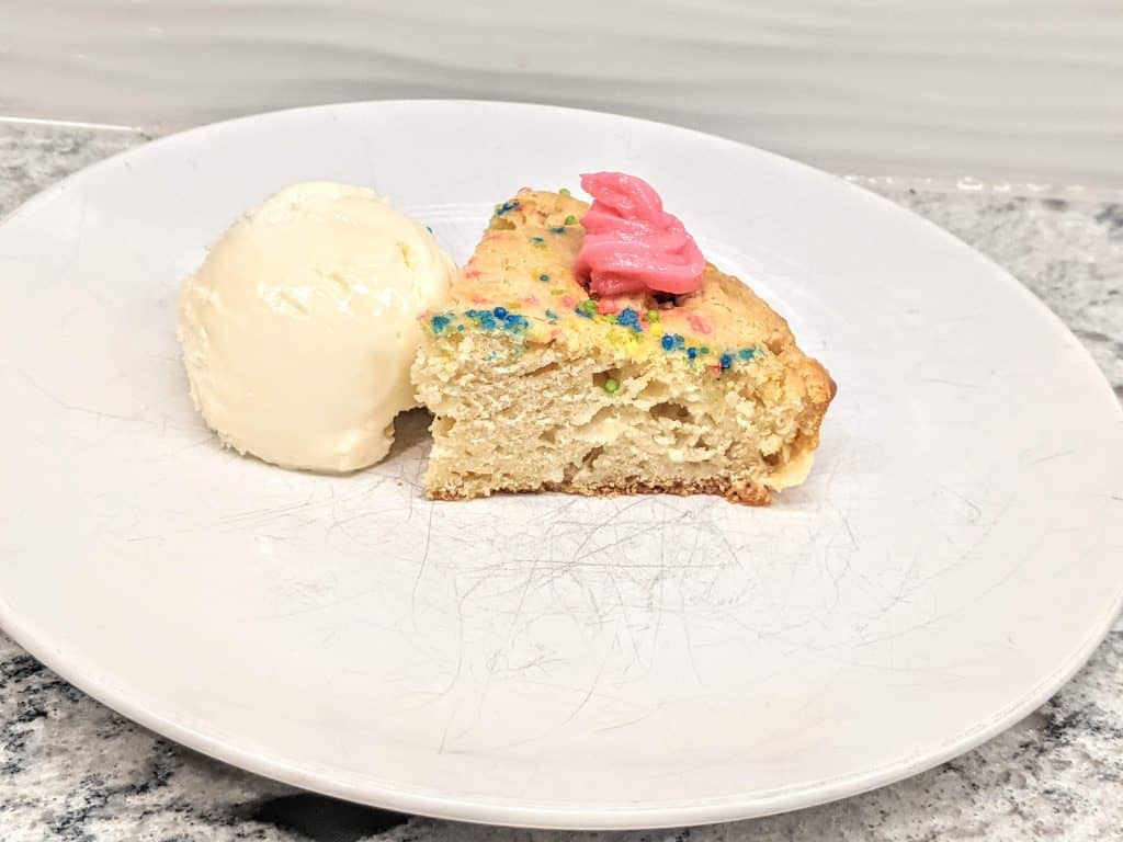 piece of white sprinkle cake plated with ice cream on side