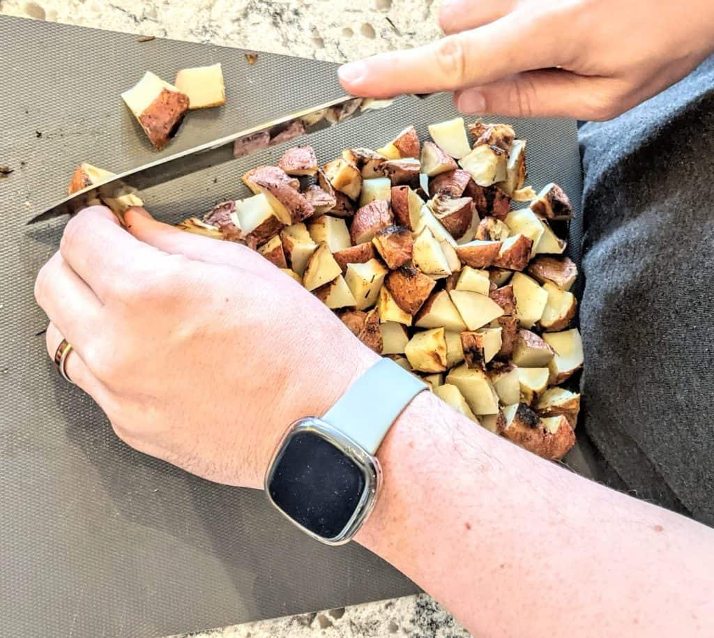 man wearing a watch chopping potatoes on a cutting board