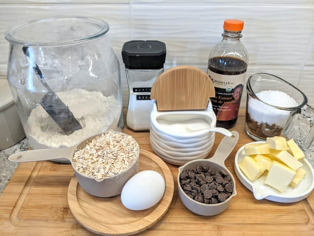 flour, baking soda, bottle of vanilla, rolled oats, chocolate chips, 1 egg, butter and 1 cup of brown and white sugar sitting on a cutting board