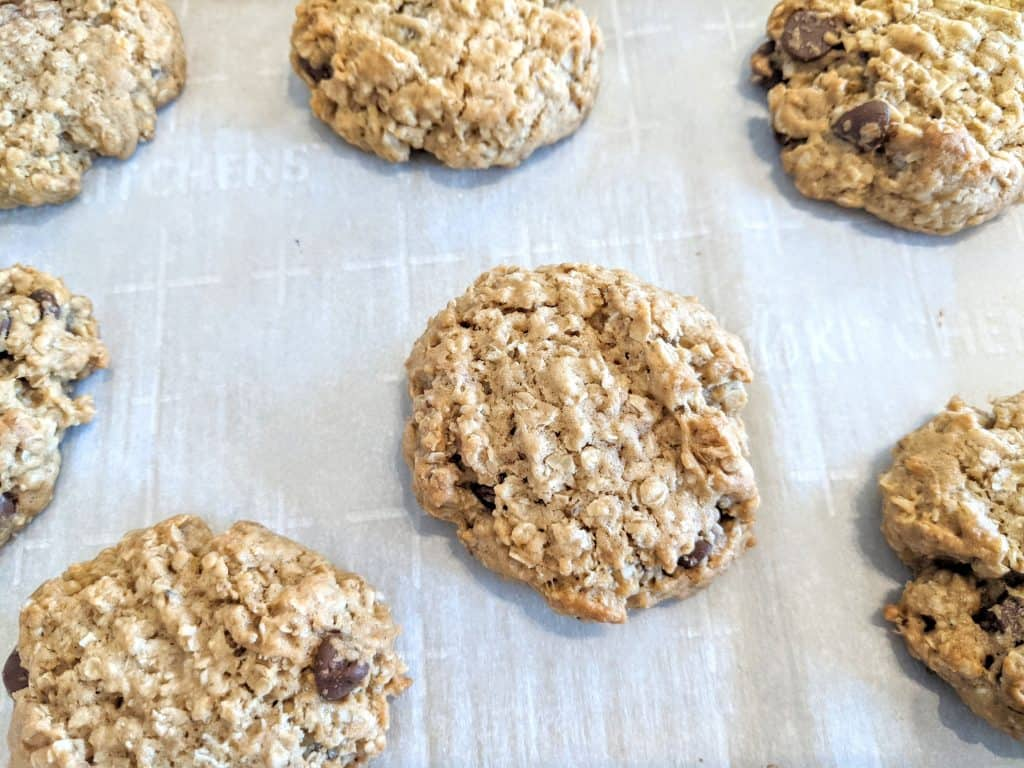 oatmeal chocolate chip cookies on baking sheet covered with parchment paper