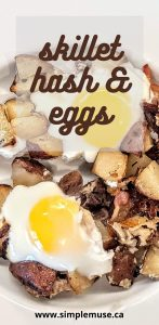 eggs with potato hash, lamb, and bacon in a cast iron skillet