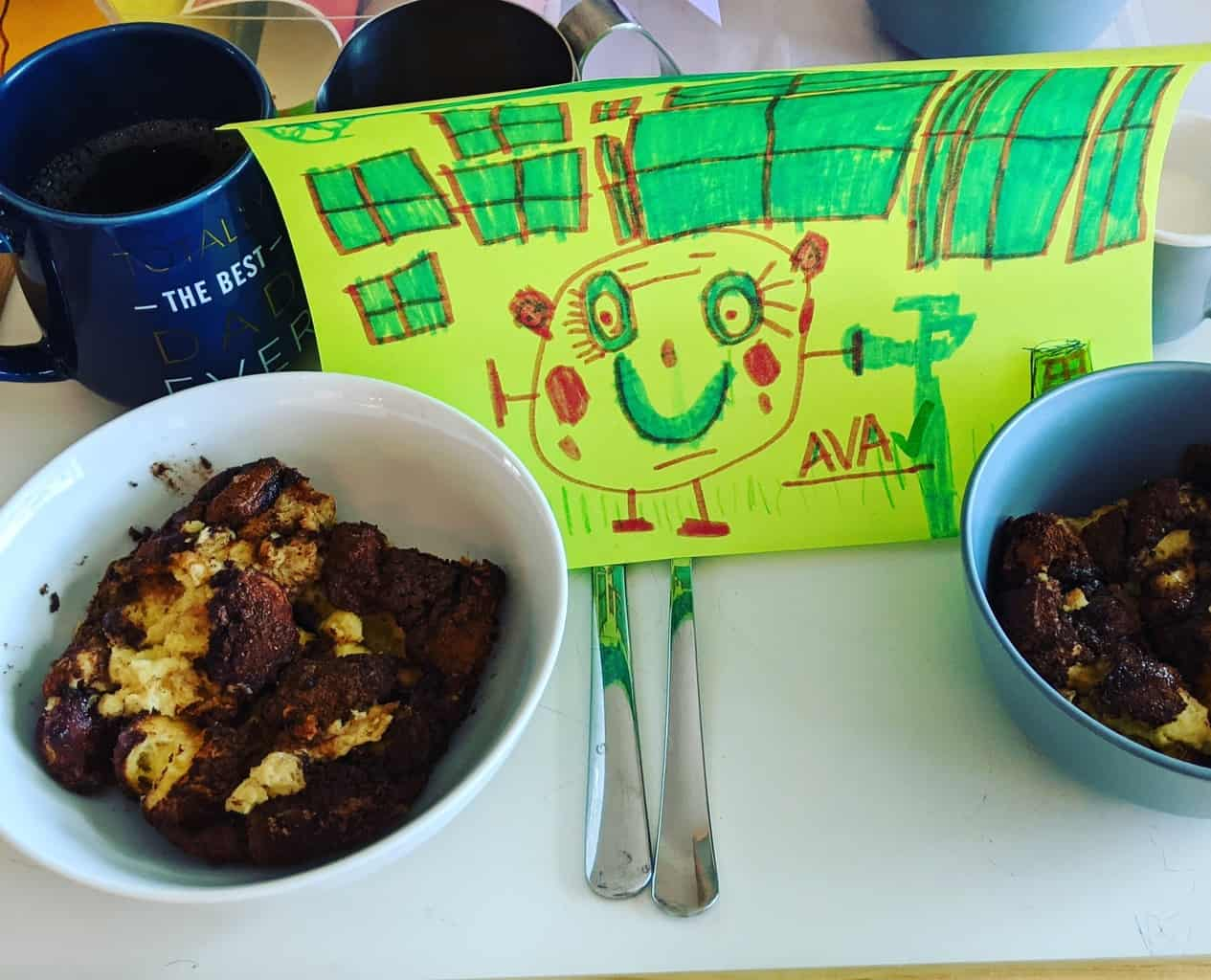breakfast of French toast casserole and coffee on a tray with a child's drawing