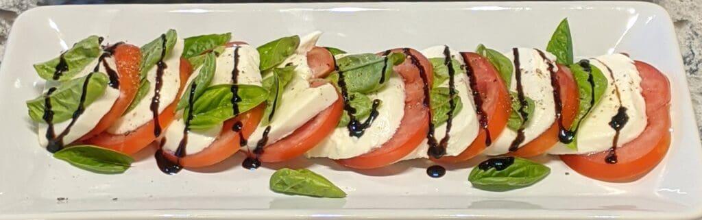 tomato, mozzarella and basil salad on a platter