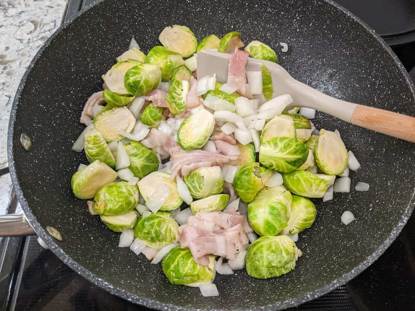 cooking brussel sprouts in a wok with onions and bacon