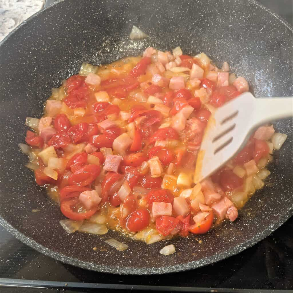mashing tomatoes in a work with onion and pancetta