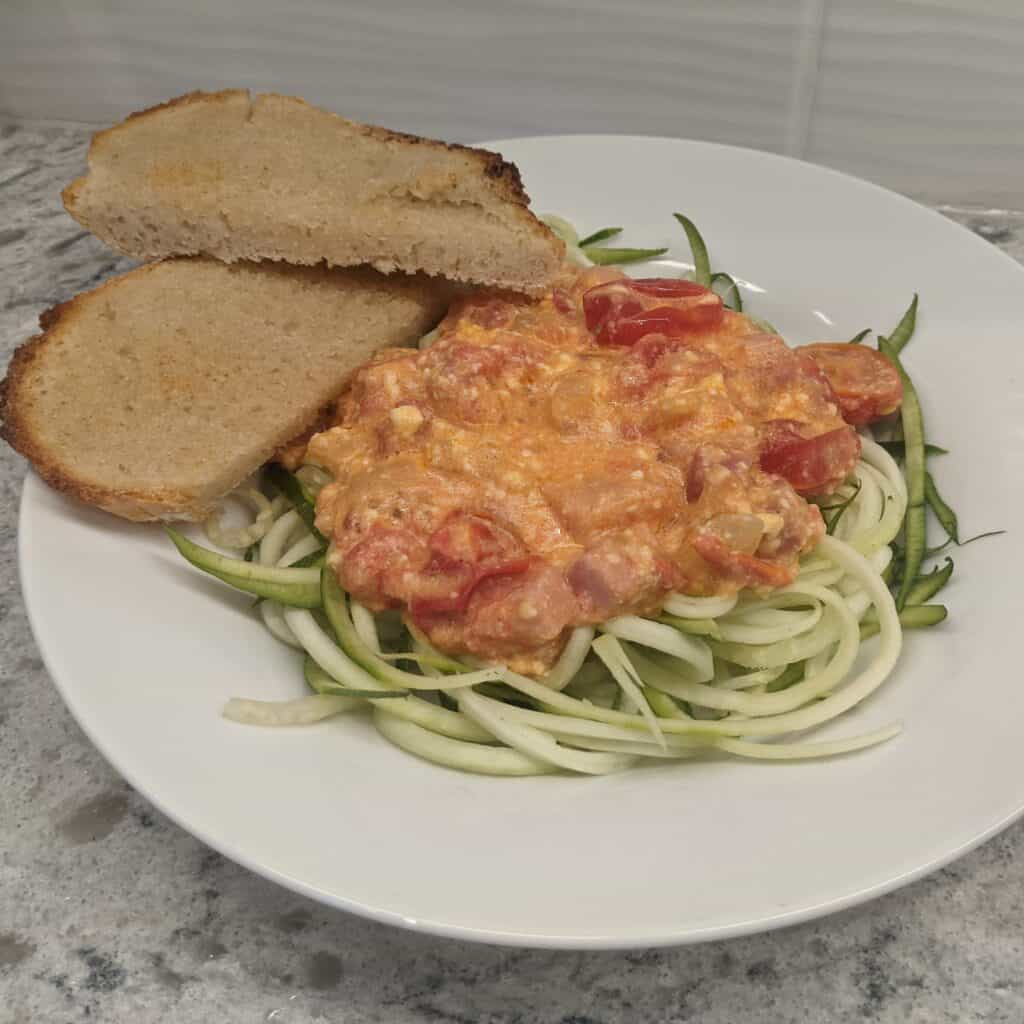 pasta sauce on zoodles with a side of garlic bread