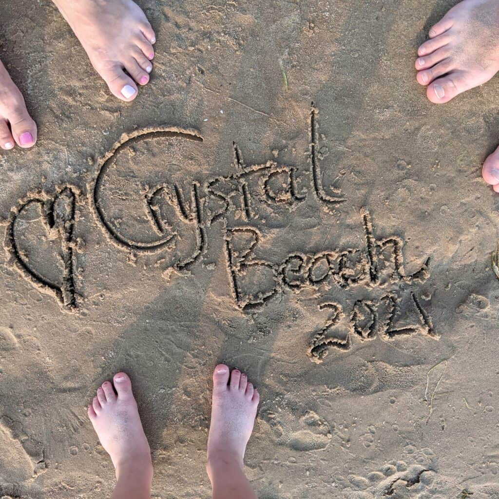 family feet standing on sand with words crystal beach 2021 written in sand