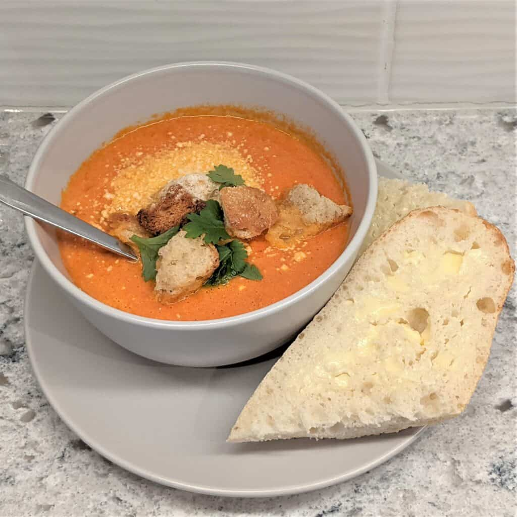 garnished roasted tomato soup in a bowl with a slice of buttered bread on a plate