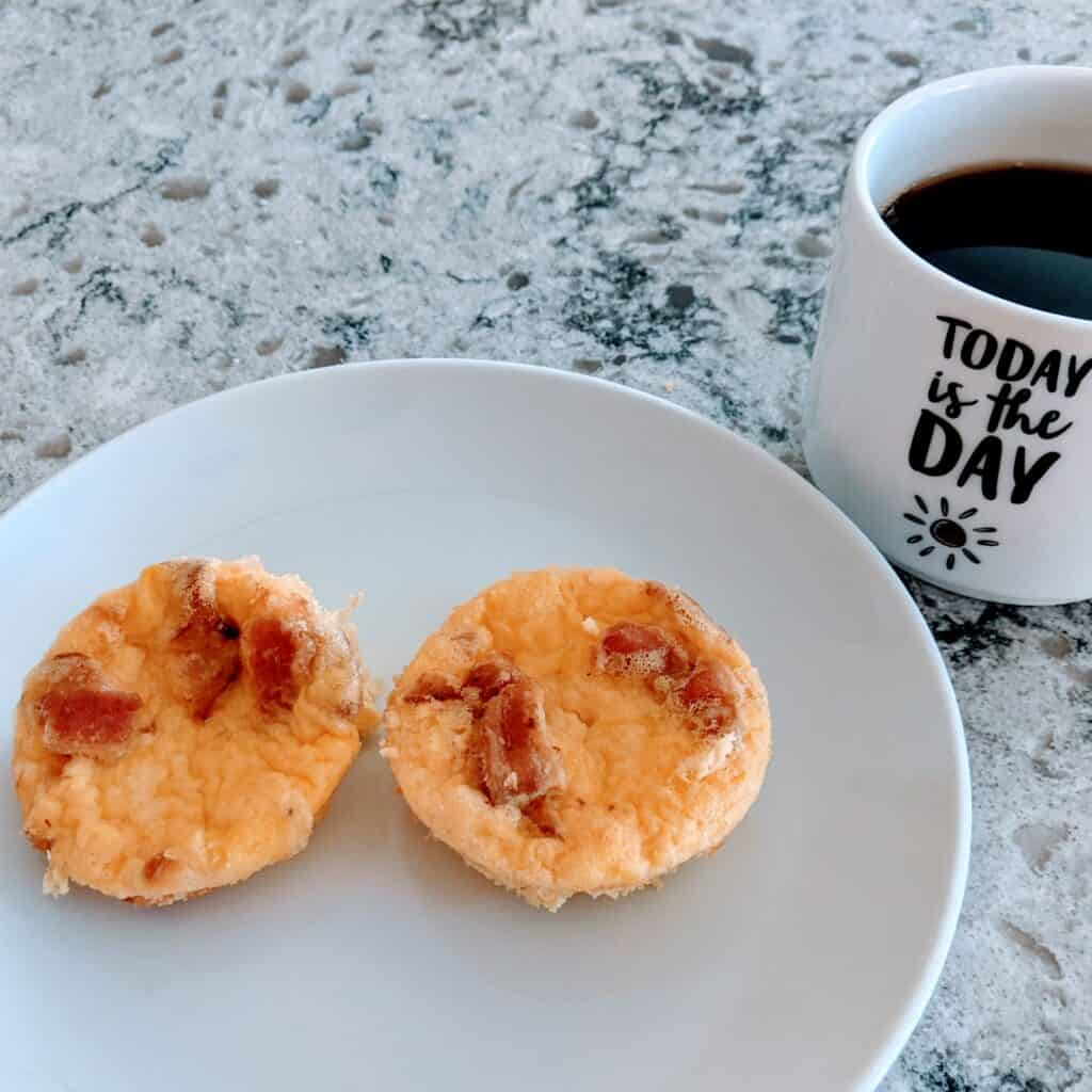 egg bites on a plate beside a cup of coffee