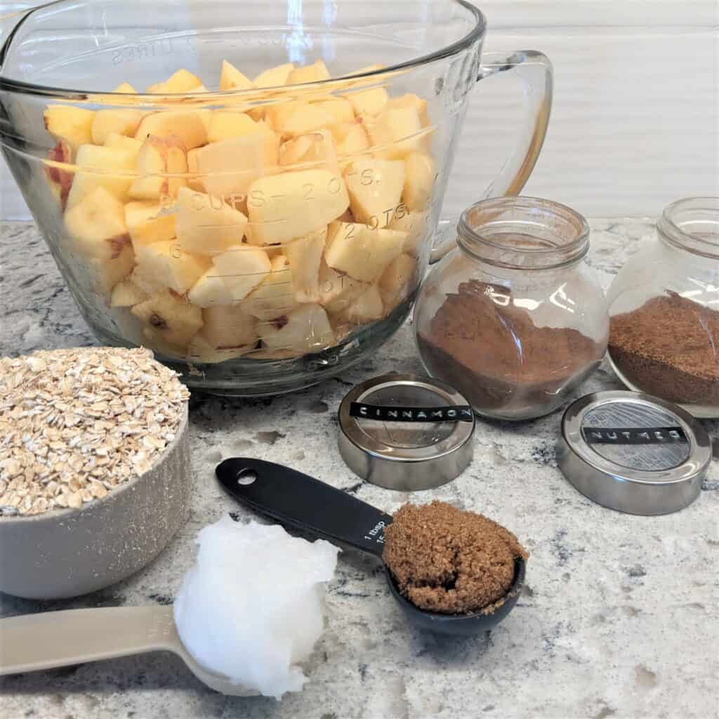 cubed apples, oats, spices, sugar and coconut oil displayed on a counter top